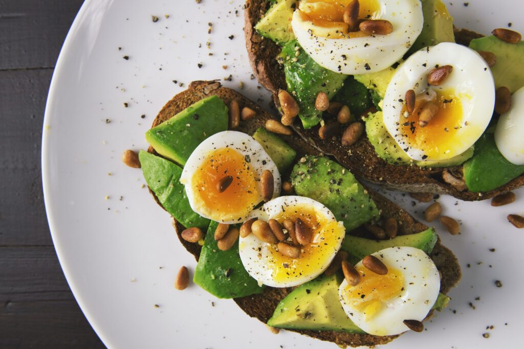 The image shows a keto diet recipe with boiled eggs, avocado, peanuts, and bread.